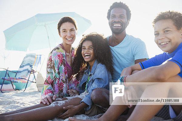 Portrait lächelnde  glückliche multiethnische Familie am Sommerstrand