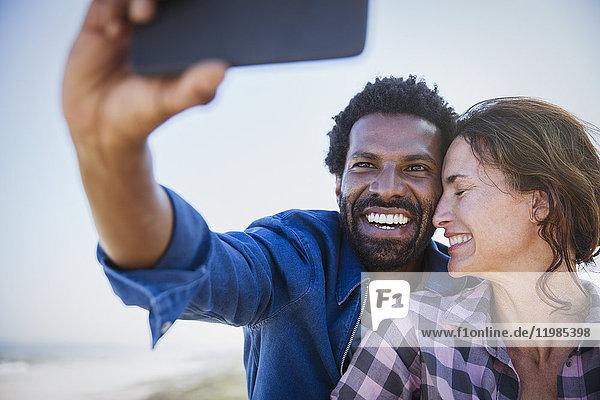 Zärtliches  fröhliches multiethnisches Paar  das sich selbst mit dem Fotohandy nimmt.
