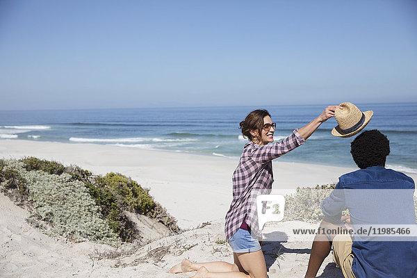Frau setzt Hut auf Freund am sonnigen Sommerstrand des Meeres