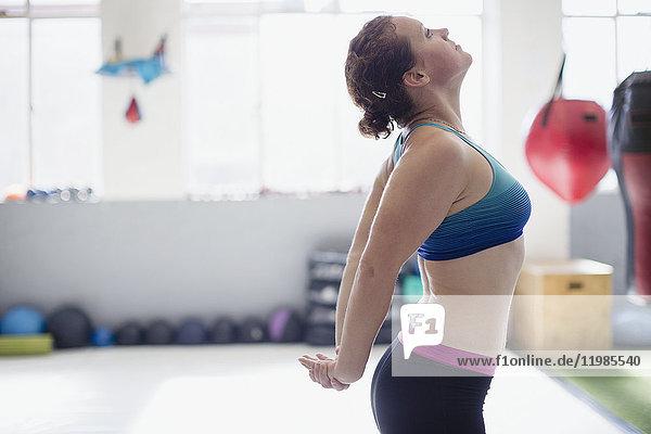Frau streckt Brust in der Turnhalle