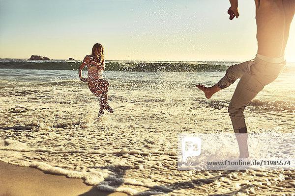 Verspieltes junges Paar beim Plantschen im sonnigen Sommer auf dem Meer