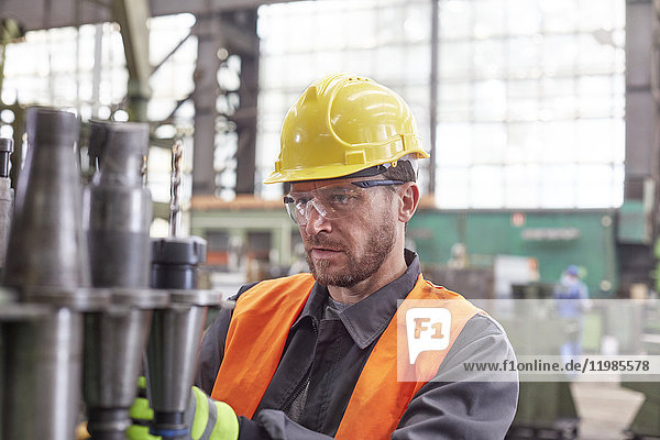 Focused male worker examining steel parts in factory