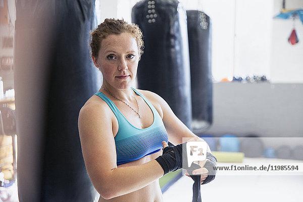 Portraitsicheres  robustes Boxerinnen-Handgelenk neben Boxsäcken im Fitnessstudio