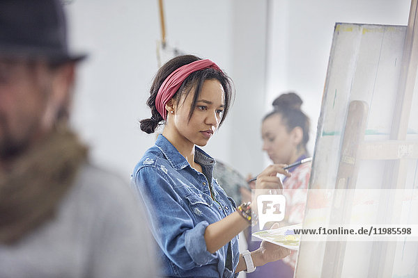 Focused female artist painting at easel in art class studio