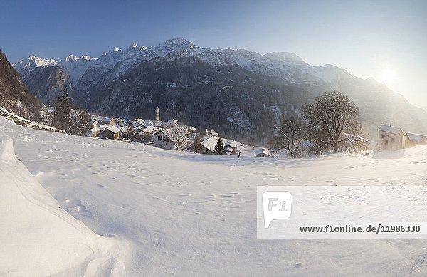 Sunset on the snowy village of Soglio canton of Graubünden Maloja District Bregaglia Valley Engadine Switzerland Europe.