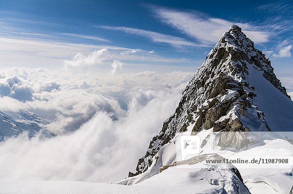 Mountain top over the clouds  Mittagorn group  Valais  Switzerland.