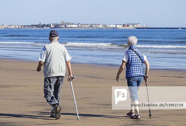 Seaton Carew  County Durham  England  United Kingdom. Elderly couple walking on beach.
