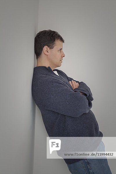 Middle age man leaning against a wall.