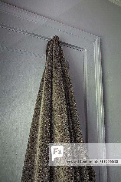 Bath towel hanging on hook on closed bathroom door.