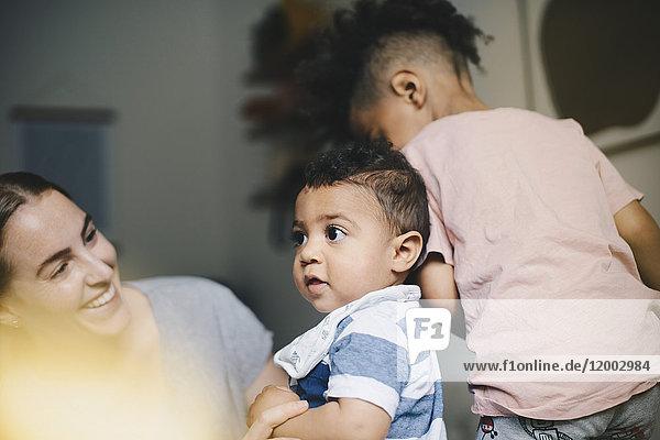 Lächelnde Mutter spielt mit Söhnen zu Hause