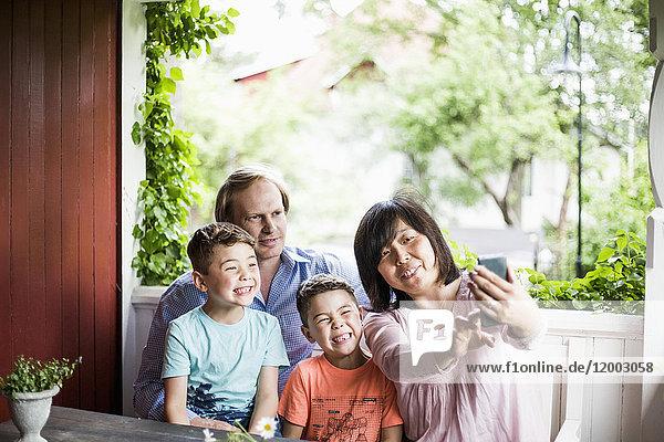 Mutter nimmt Selfie mit Familie in der Veranda auf