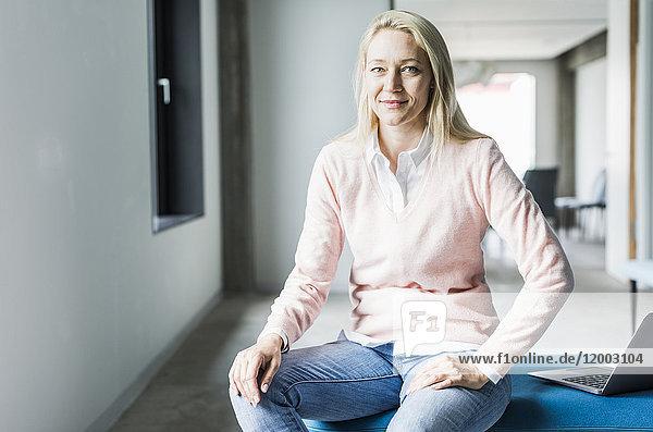 Portrait einer selbstbewussten Geschäftsfrau mit Laptop