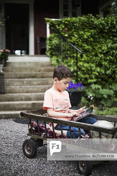 Junge mit digitalem Tablett beim Sitzen im Wagen gegen Haus