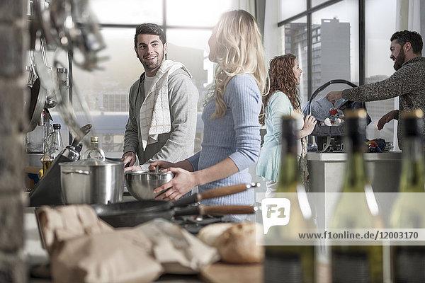 Paar beim Kochen in der Küche mit der Familie im Hintergrund