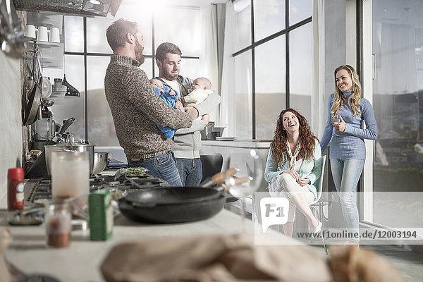 Zwei Frauen beobachten Ehemänner  die ihre Babys in der Küche halten.