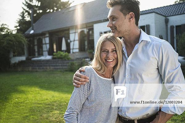 Glückliches Paar im Garten ihres Landhauses