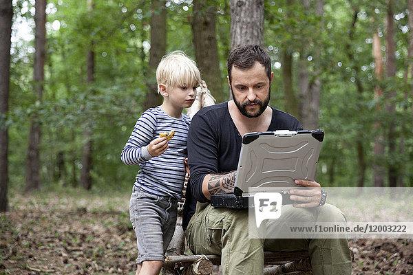 Vater und Sohn sitzen auf einem selbstgebauten Holzstuhl im Wald mit Laptop