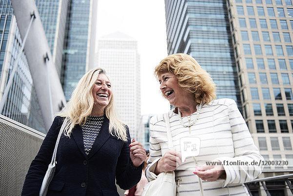 UK,  London,  zwei glückliche Geschäftsfrauen in der Stadt