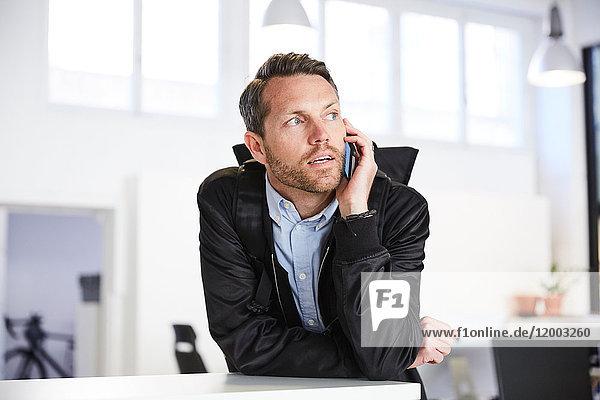 Seriöser Geschäftsmann beim Telefonieren im Kreativbüro