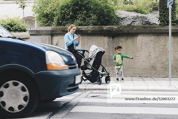 Mutter mit Handy im Stehen mit Sohn und Kinderwagen auf dem Bürgersteig in der Stadt