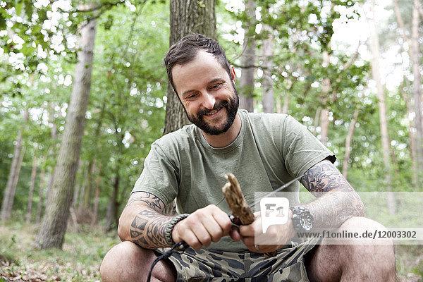 Lächelnder Mann beim Schnitzen im Wald
