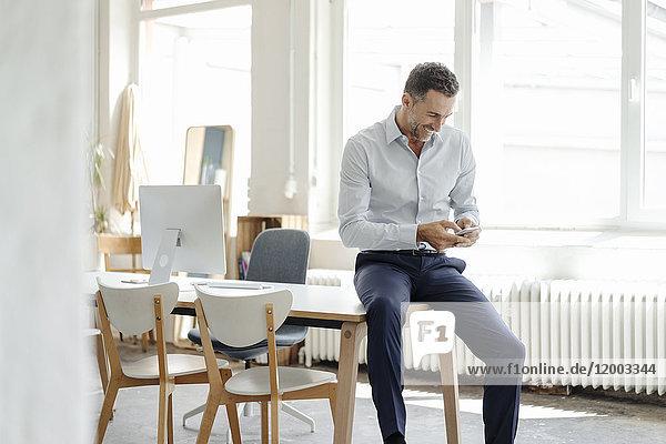 Lächelnder Geschäftsmann im Büro beim Blick aufs Handy