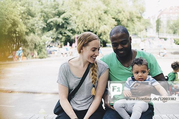 Lächelnde Eltern sitzend mit Kleinkind im Park