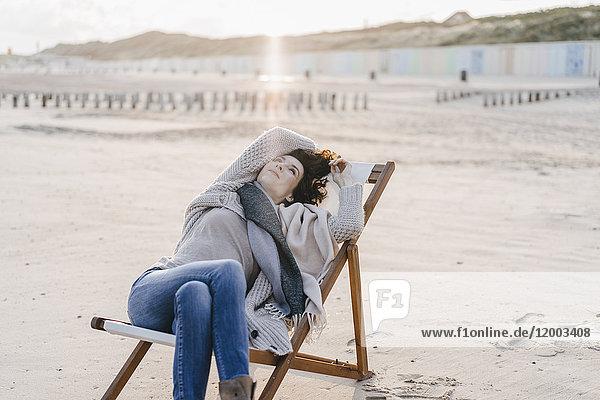 Frau auf Liegestuhl am Strand sitzend
