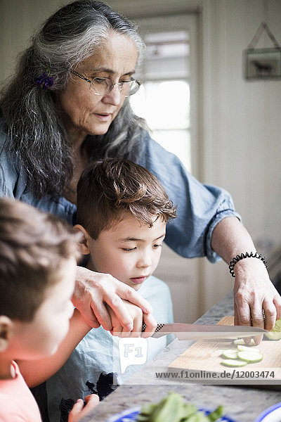 Großmutter hilft Enkel beim Gurkenschneiden in der Küche zu Hause