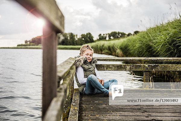 Mädchen am Steg am See sitzend