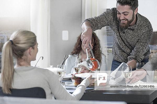 Mann serviert Essen für Freunde am Esstisch