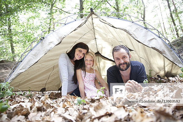 Porträt einer glücklichen Familie mit Tochter im Zelt im Wald