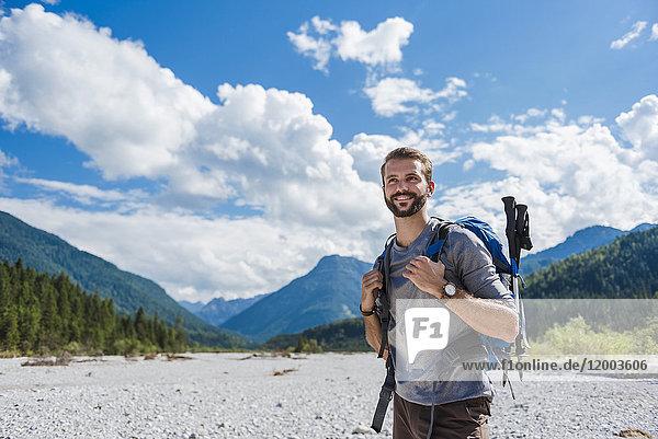 Deutschland  Bayern  Portrait junger Wanderer mit Rucksack und Wanderstöcken