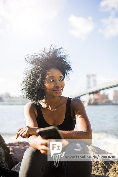 USA  New York City  Brooklyn  lächelnde Frau mit Handy am Wasser sitzend