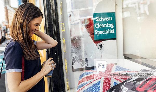 UK  London  Portobello Road  lächelnde junge Frau beim Schaufensterbummel