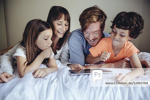 Kinder und ihre Eltern schauen sich die Tablette auf dem Bett an.