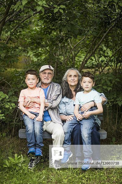 Porträt von Großeltern  die mit Zwillingseltern auf einer Bank gegen Pflanzen im Garten sitzen.