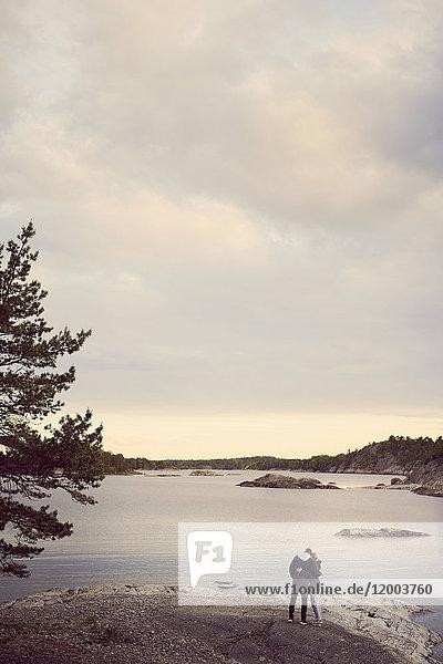 Rückansicht des am Strand stehenden Paares gegen den Himmel bei Sonnenuntergang