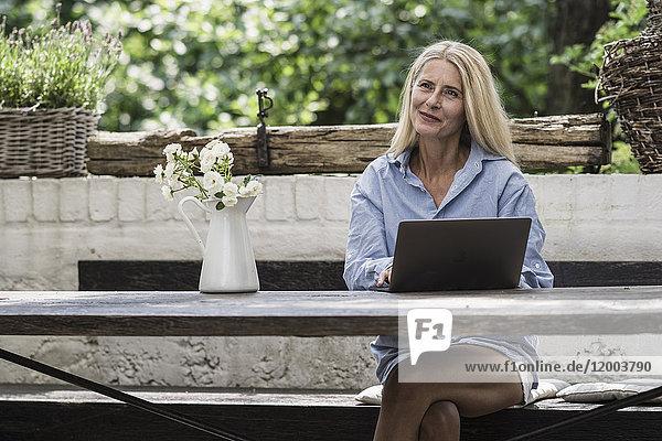 Reife Frau auf der Terrasse sitzend  mit Laptop
