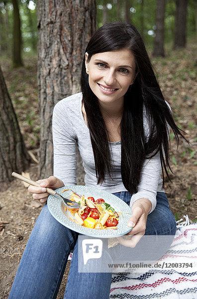 Porträt einer lächelnden Frau  die bei einem Picknick im Wald Nudelsalat isst.