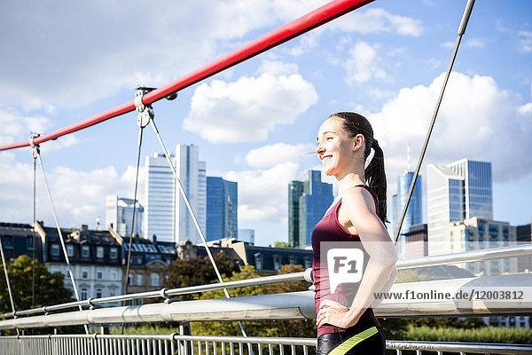 Deutschland  Frankfurt  sportliche junge Frau auf der Brücke stehend