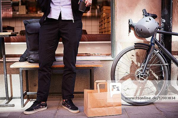 Niedriger Abschnitt des Geschäftsmannes  der auf dem Bürgersteig in der Stadt mit Papiertüte und Fahrrad steht. Niedriger Abschnitt des Geschäftsmannes, der auf dem Bürgersteig in der Stadt mit Papiertüte und Fahrrad steht.
