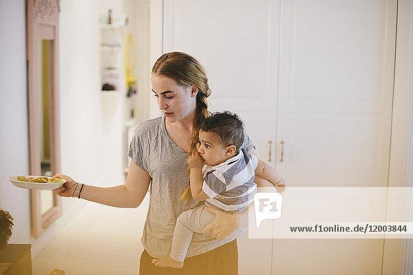 Mutter  die den Sohn trägt  während sie den Teller zu Hause hält.