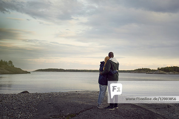 Rear view of couple standing at beach while looking at lake against sky during sunset