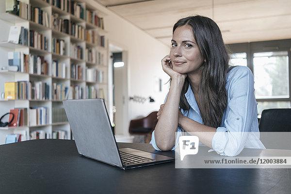 Porträt einer lächelnden Frau am Tisch mit Laptop