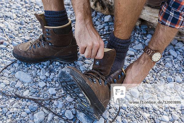 Wanderer beim Anziehen der Schuhe  Teilansicht