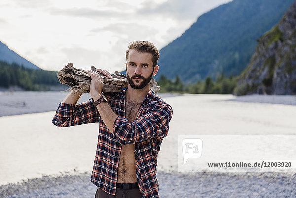 Deutschland  Bayern  Porträt eines jungen Mannes mit Brennholz auf der Schulter in der Natur