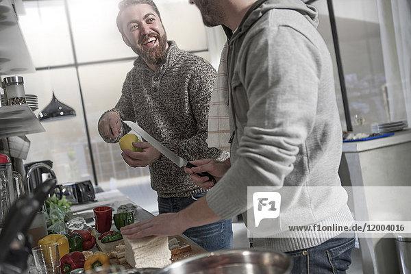 Zwei glückliche Männer bereiten eine Mahlzeit in der Küche zu.