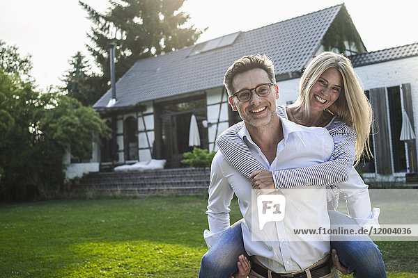 Portrait of happy mature couple on meadow in front of their house