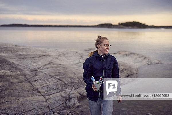 Junge Frau beim Spaziergang mit Zahnbürste und Zahnpasta am Strand bei Sonnenuntergang